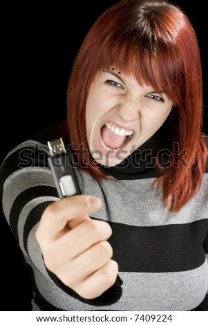 Beautiful redhead girl holding an usb memory stick or flash drive at the camera with an angry expression. Studio shot. - stock photo
