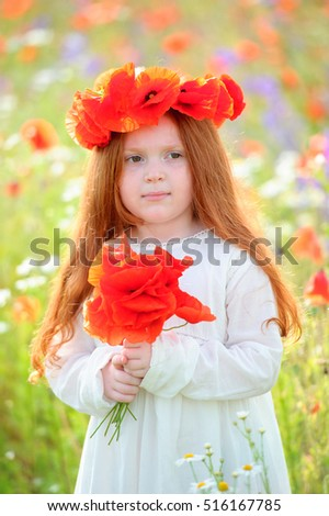 Beautiful redhead girl in a field with flowers