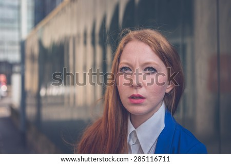 Beautiful redhead girl in blue jacket posing in an urban context - stock photo
