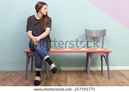 Beautiful redhead girl left alone on a two seats bench. Looking sad to the empty seat. - stock photo