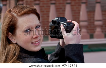 Beautiful redhead girl taking a shot with a modern DSLR camera