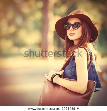 Beautiful redhead girl with bag in the park. - stock photo