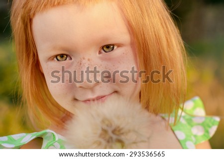 beautiful redhead girl with dandelion in his hands