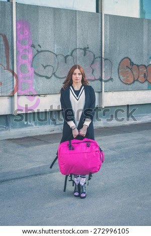 Beautiful redhead girl with long hair and blue eyes carrying a big bag in an urban context - stock photo