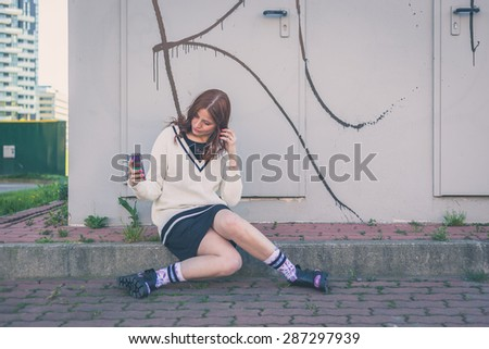 Beautiful redhead girl with long hair and blue eyes taking a selfie in an urban context - stock photo