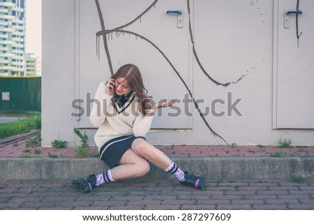 Beautiful redhead girl with long hair and blue eyes talking on phone in an urban context - stock photo