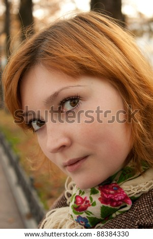 Beautiful redhead girl wondering in an autumn park