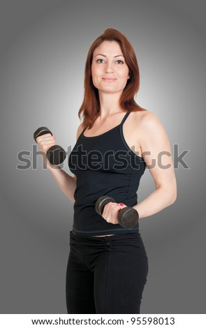 Beautiful redhead lifting hand weights - stock photo