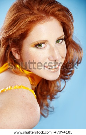 Beautiful redhead on blue background - stock photo