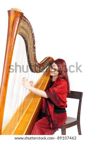 Beautiful redhead playing a wooden harp isolated on white