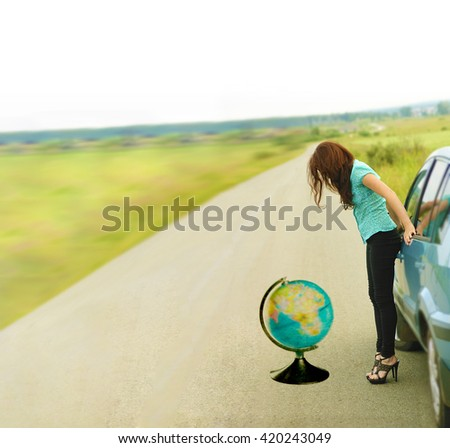 Beautiful redhead sexy woman, has black trousers and blue shirt , long hair, legs and elegant slim body, stand to road near car above globe map. Real lady driver. Sunny day. no face. unrecognizable - stock photo