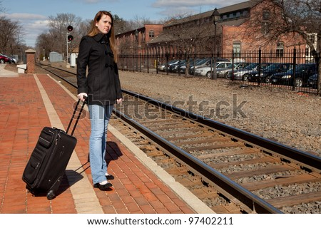 Beautiful redhead with her luggage waiting for the train