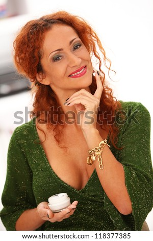 Beautiful redhead woman applying cream on a face in studio