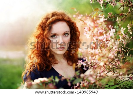 beautiful redhead woman in a blossoming garden - stock photo