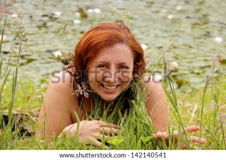 Beautiful redhead woman laying in the grass near the lake with water lilies  - stock photo