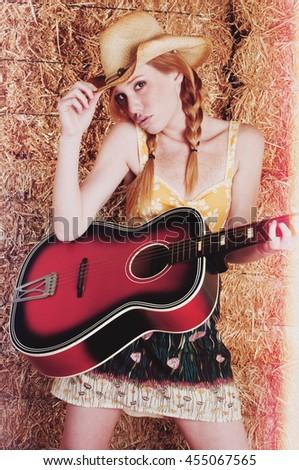 Beautiful redhead woman playing guitar - stock photo
