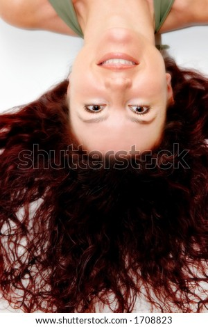 Beautiful redhead woman smiling with long curly hair on white background - stock photo
