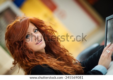 Beautiful redhead woman using tablet in public library.  - stock photo