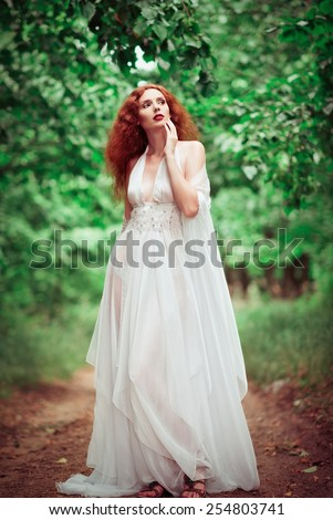 Beautiful redhead woman wearing white dress, in the forest - stock photo