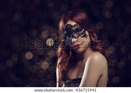 Beautiful redhead woman with black laced mask. Retro filter. - stock photo