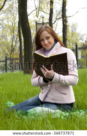 Beautiful redhead woman with book in park