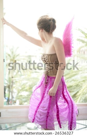 Beautiful redhead woman with pink feather wings on romantic soft light - stock photo
