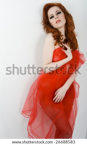 Beautiful redhead woman with red drapery - stock photo