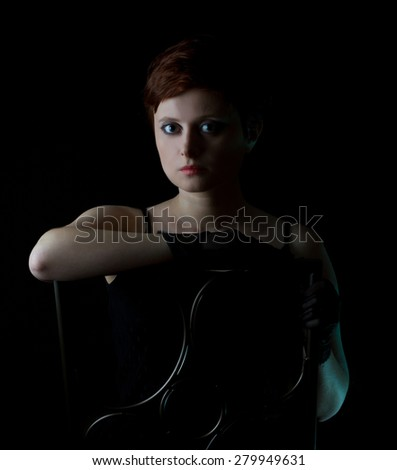 Beautiful redhead woman with short hair in studio on black background sitting on a chair - stock photo
