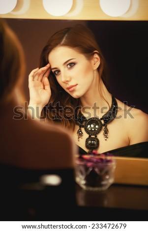 Beautiful redhead women applying makeup near mirror - stock photo