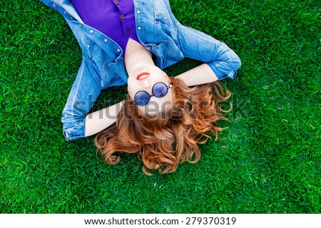 Beautiful redhead women lying down on green grass in summer time in the park. - stock photo