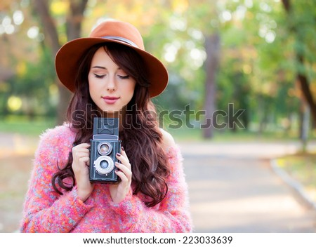 Beautiful redhead women with camera in autumn park. - stock photo