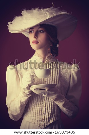 Beautiful redhead women with cup of tea - stock photo