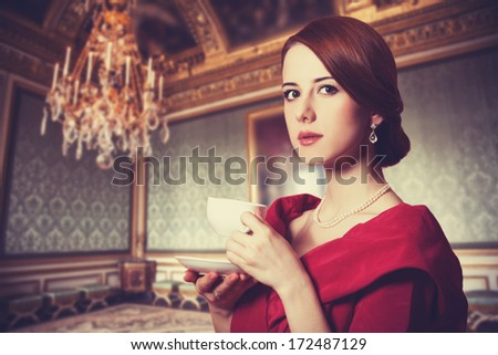 Beautiful redhead women with cup of tea. Photo in old color image style. - stock photo