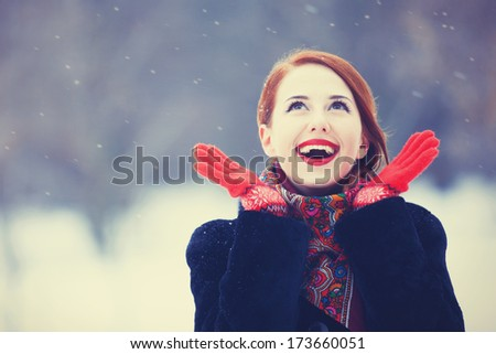 Beautiful redhead women with in winter park. Outdoor photo. - stock photo