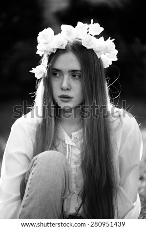 Beautiful redhead young woman in a deep thought in the summer park