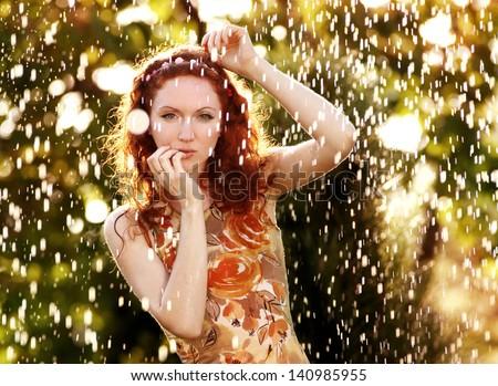 beautiful redhead young woman in rain drops - stock photo