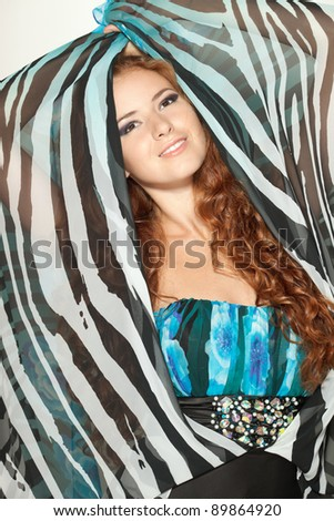 Beautiful redheaded fashion model posing in chiffon dress - stock photo