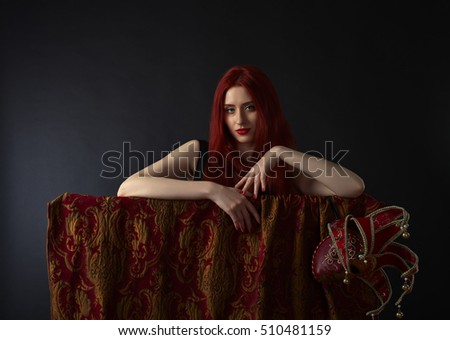 Beautiful redheaded woman in a black dress with carnival mask
