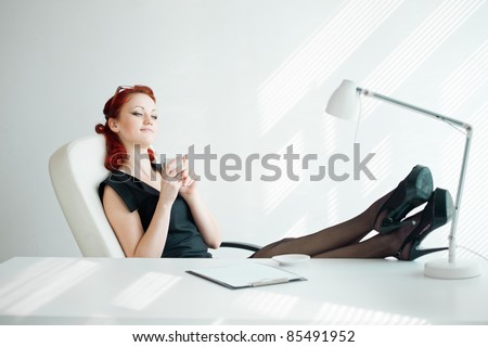 Beautiful redheaded woman in the workplace with a cup of coffee - stock photo