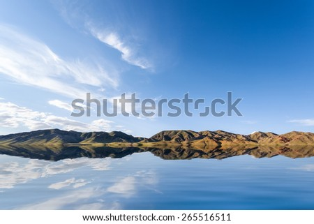 beautiful reflection on the lake against a blue sky in inner mongolia - stock photo