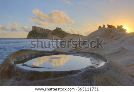 Beautiful reflections of sunrise sky on a mirror-like rock formation at the rocky beach of Yehliu Coast in northern Taiwan ~ Dramatic scenery of peculiar coastline in northern Taiwan - stock photo