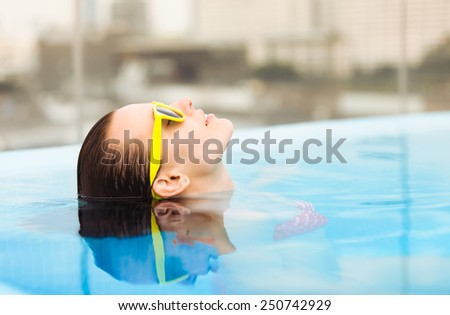 Beautiful relaxed woman floating in the swimming pool - stock photo