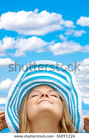 Beautiful relaxed woman  wearing a hat outdoors - stock photo