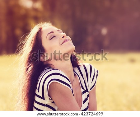 Beautiful relaxing woman sitting on the grass  and enjoying fresh air in sunny summer day on nature background - stock photo