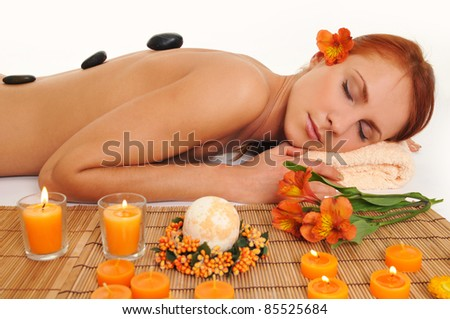 Beautiful relaxing woman with stones on her back in a Spa - stock photo