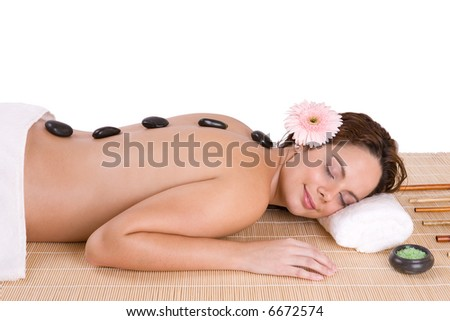Beautiful relaxing woman with zen stones on her back in a Spa - Beauty and Spa