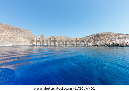 Beautiful remote tropical island paradise seen from a cruise ship offshore with its wake rippling the surface of the calm blue ocean - stock photo
