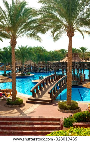 Beautiful resort place - swimming pool with tropical palm garden. Multicolored summertime vibrant vertical outdoors image.  Egypt. Sharm-el-sheikh. - stock photo