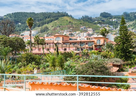 Beautiful resort with hill behind it in Madeira.  Scenic view of beautiful tan colored building or resort hotel with tall grassy hill behind it in Madeira Portugal - stock photo