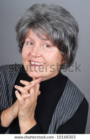 Beautiful retired woman sitting for a happy, carefree portrait - stock photo